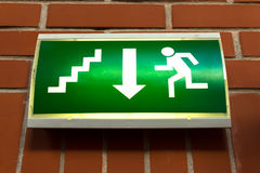 Green emergency exit sign. On the wall Stock Photography