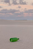 Green Bottle. A Green Empty Bottle on Sand Royalty Free Stock Photography