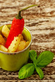 Green enameled cup with potato fries decorated with a red chilly pepper and basil leaves, over wooden table. Vertical. Top view. Royalty Free Stock Photography