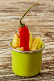 Green enameled cup with potato fries decorated with a red chilly pepper, over wooden table. Vertical. Side view. Royalty Free Stock Photos