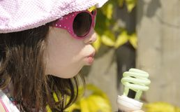 Green energy. Concept to illustrate green energy by a little girl blowing on a compact fluorescent lightbulb Royalty Free Stock Images
