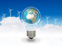 Green energy. Theme of the earth inside a clear light bulb, with a background of wind turbines, clouds and blue sky Stock Images