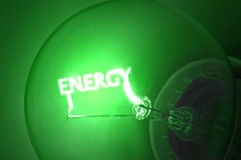 Green energy. Close up on illuminated green light bulb filament which spells the word ENERGY Royalty Free Stock Images