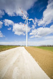 Green Energy. Modern wind energy plant on green fields with a clouds in the background stock photos