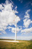 Green Energy. Modern wind energy plant on green fields with a clouds in the background royalty free stock images