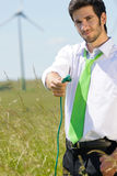 Green energy businessman in field hold plug royalty free stock photos