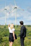 Green energy businesspeople in field show windmill Stock Photography