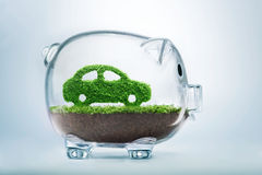 Green energy car. Green energy concept with grass growing in shape of car inside transparent piggy bank Stock Images