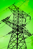 Green energy is clean environment. High voltage electricity pylon silouette against green background Stock Images