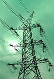 Green energy is clean environment. High voltage electricity pylon silouette against green background Stock Image