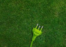 Green energy concept. Green power plug on a green grassland Stock Photo