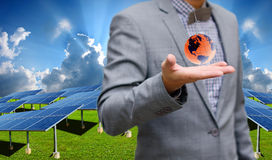 Green energy concept, Businessman carry world of wind turbine Stock Image
