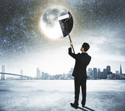 Green energy concept with businessman cleans the Moon at city ba Royalty Free Stock Image