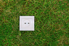Green energy concept: electric outlet on a grass Royalty Free Stock Photography