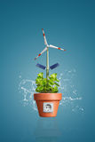 Green Energy Concept. Front view of a  flower pot with an electrical outlet. Inside the pot is a green plant and a windmill with solar panels resembling a flower Royalty Free Stock Photos