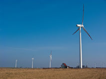 Green energy for a country house. Country house powered with green energy (windmill or wind turbine). Conceptual image Stock Photos