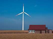 Green energy for a country house. Country house powered with green energy (windmill or wind turbine). Conceptual image Royalty Free Stock Photo