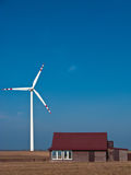 Green energy for a country house. Country house powered with green energy (windmill or wind turbine). Conceptual image Stock Photography