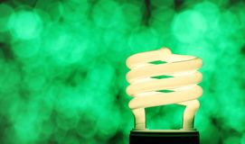 Green energy efficiency. Illuminated compact fluorescent lamp  - CFL - on a background of de-focused green lights symbolising energy efficiency - with copy space Stock Photos