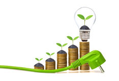 Green Energy. A green electricity plug with stack of golden coins and a young plant in a lightbulb / Green energy creating wealth concept Stock Photo