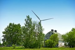 Green Energy Farm. Green Energy and Old Farm Barn Between Threes. Modern Wind Turbine in Background Royalty Free Stock Image