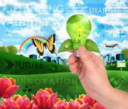 Green Energy Light Bulb Background. A hand is holding a green light bulb against a city. The lightbulb represents green energy and conservation. There is a Royalty Free Stock Photography
