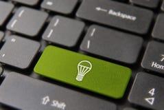 Green energy light bulb on computer keyboard Royalty Free Stock Photos