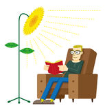 Green Energy. Man reading a book in his chair with light like a sunflower, meaning energy from ecological sources Stock Photography