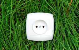 Green energy outlet. White outlet on green grass background royalty free stock photos