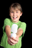 Green energy sources. A boy wearing a green t-shirt hiolding a green energy efficient light bulb royalty free stock images