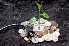 Green energy. A tree growing from a socket with coins and a plug / green energy / save the world stock illustration