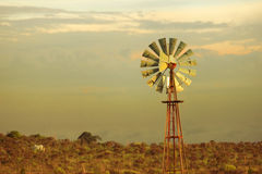 Green energy vintage wind mill sunset background Stock Photos