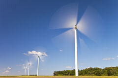 Green Energy Wind Turbines In Field of Sunflowers. A farm of wind turbines or windmills providing alternative sustainable green energy, situated in a field of Royalty Free Stock Image