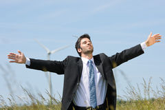 Green energy - Young businessman in field windmill Stock Photography