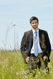 Green energy - Young businessman in field windmill Stock Photo