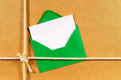 Green envelope with message note card or label, brown paper package background, copy space Stock Images