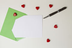 Green envelope, message, pen and small red hearts on white table. Love letter, valentines day concept Stock Photos