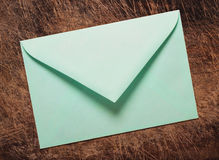 Green envelope on wooden table. Royalty Free Stock Image