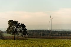 Green environment tree panorama view over wind farm landscape in Germany with white generator turbines. Green environment tree panorama view over a wind farm Royalty Free Stock Photo