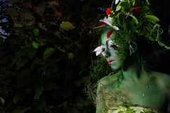 Green environmental face painting. Green face painting environmental floral and dark with flowers in her hair Royalty Free Stock Photo