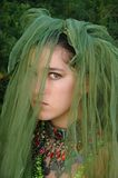 Green With envy. Mysteriously saddened girl with a green veil covering her face Stock Photos