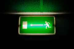 Green escape exit. On black background glowing in the dark green light royalty free stock images