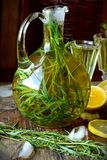 Green estragon lemonade pitcher a wooden table Stock Images