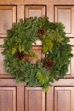 Green Evergreen Christmas Wreath On Wooden Door. Green Christmas Wreath Hanging On Wooden Door royalty free stock image