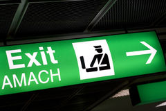 Green Exit sign in airport Royalty Free Stock Image