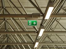 Green Exit Sign under Grid Roof with Lamps Stock Images