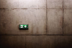 Green exit sign on the wall. Green exit sign on the beton wall Royalty Free Stock Photography