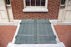 Green Exterior Storm Cellar Doors. Green cellar doors outside a brick home, under a window Royalty Free Stock Photo