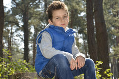 The green-eyed boy sitting in the woods. Royalty Free Stock Images