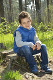 The green-eyed boy sitting in the woods. Stock Photo